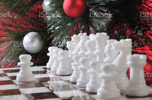 The initial position the white chess pieces with the first step of a pawn on the cell E4. The background is the Christmas tree, decorated with balloons.